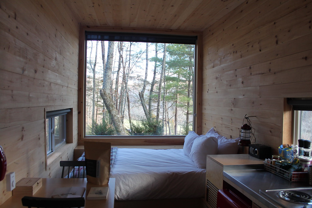 A tiny house features a large picture window into the forest and a white bed