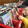 "KEVIN HARVISON | Staff photo<br /> Two-year-old Dek McAfee says he ""likes movies"" as he looks over some of the DVD's at the McAlester Public Library childrens section."