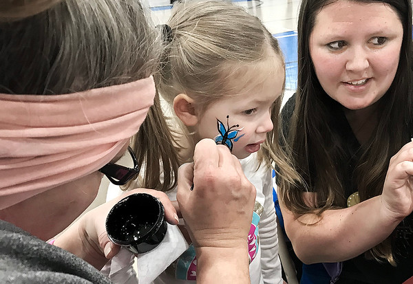 KEVIN HARVISON | Staff photo<br /> Carly Wilson, center, holds still while getting her face painted during the Santas Helper Fair Saturday.