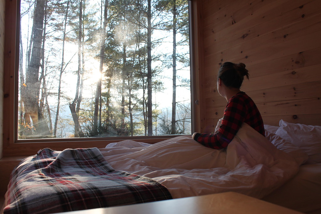A girl wears pajamas with blankets around her, looking out the window at the forest