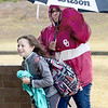 KEVIN HARVISON | Staff photo<br /> Parker Middle School employee Rhonda Thompson follows student Kinley Smart to shelter from the rain Thursday morning.