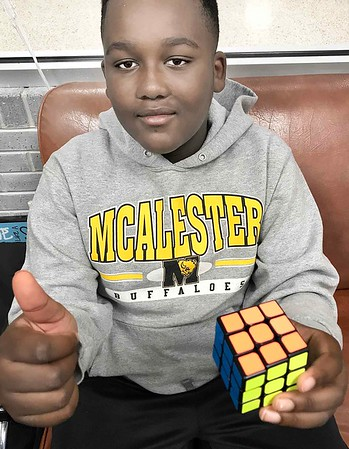KEVIN HARVISON | Staff photo<br /> Asyiah Spencer, fifth grade student at Parker Intermediate School, gives a thumbs up after finishing the Rubik's Cube in under a minute for the second time. The Rubik's Cube is a 3-D combination puzzle. The puzzle was originally advertised as having over 3,000,000,000 three billion combinations but only one solution. Depending on how combinations are counted the actual number can be significantly higher.