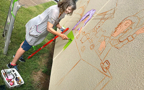 KEVIN HARVISON | Staff photo<br /> Artist Anita Jackson starts on a mural of children book characters outside the McAlester Public Library Monday. The project is sponsored by Pride in McAlester.
