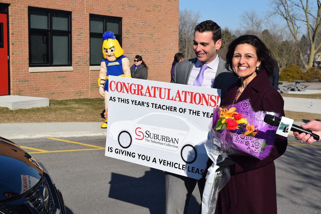 . Lisa Rice, a first grade teacher at Village Oaks Elementary in Novi, stands with Che Shaydak, general sales manager of The Suburban Collection, as she\'s named the school district\'s 2018 Teacher of the Year on Monday, March 26, 2018. As part of the honor,  The Suburban Collection will provide her with a leased vehicle of her choice for a two or three years. (Mark Cavitt/The Oakland Press)