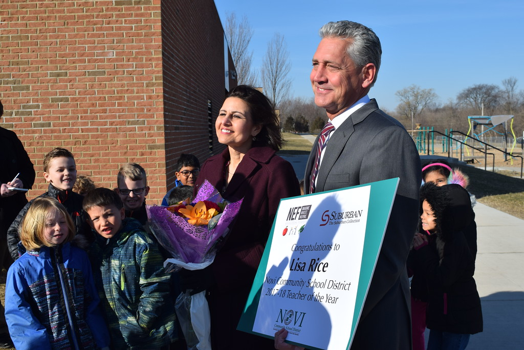 . Lisa Rice, a first grade teacher at Village Oaks Elementary in Novi, stands with Tom Smith, chair of the Novi Educational Foundation, and her students, as she\'s named the school district\'s 2018 Teacher of the Year on Monday, March 26, 2018. As part of the honor,  The Suburban Collection will provide her with a leased vehicle of her choice for a two or three years. (Mark Cavitt/The Oakland Press)