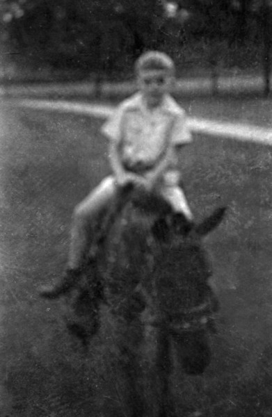 """Boy on a Donkey  <div class=""""gg_commentary"""">Though the pictures are badly degraded, to me this only adds to their charm and their poignancy. What remains on the film is what can never be captured on the film in the first place — not the details of faces and places, but the spirits of people who laughed and cried where I now laugh and cry with my own family. In a sense the pictures are just snapshots of special moments — a girl's birthday party, a family vacation — just a few brief days in the lives of an American family. These are same things we all take pictures of, memorials of days we can never forget.</div>"""