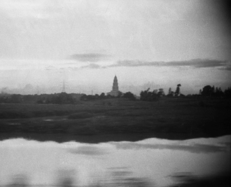 Passing a Tall Building in a Flat Land, Water in the Foreground