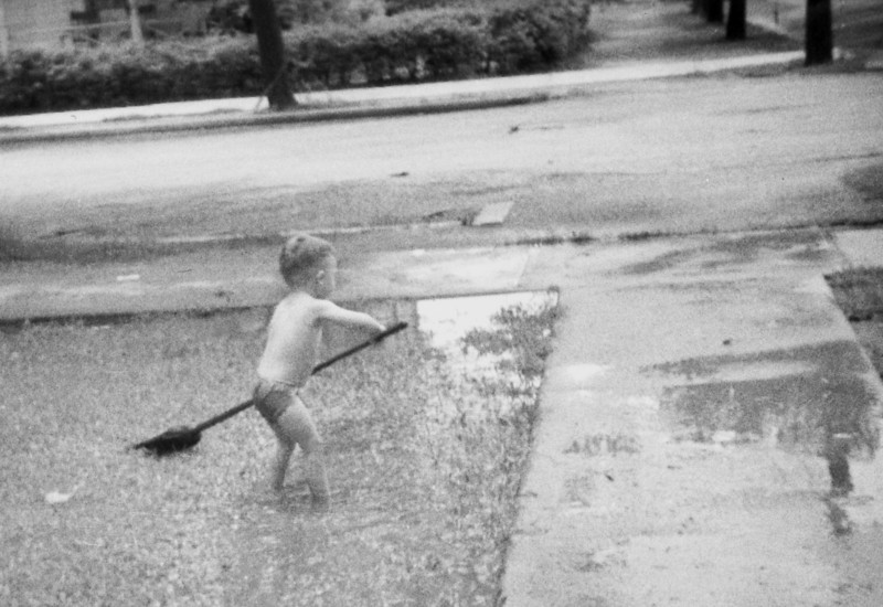 Boy Playing with Broom in Puddle