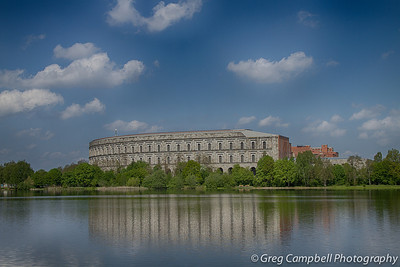 """This was my first glimpse of """"Congress Hall"""" as I came around the west corner of Zeppelin Field and was able to see across the water. Congress Hall was built by the Nazi party to house congress. It was never finished. It is an impressively HUGE structure - for 1935 or any age...   It is horse shoe shaped, and the final structure was suppose to have a full roof over top the entire thing. Today, the inner horse shoe remains exposed to the sky."""