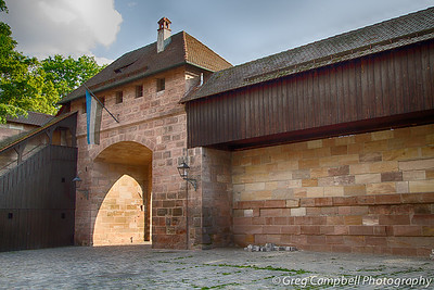 """This is one of the entrances of the ancient """"town market"""" of Nuremberg. To and from dinner each night, I pass through this square of high walls. Ghosts of carts full of meat, vegetables and other goods as well as people and children cramming the market on a normal day dance through my mind when I pass through."""