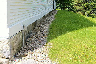 Photo 6  North wall: granite foundation stones to be used for new veneer; border and slope to be re-graded and improved; frame issues apparent in siding
