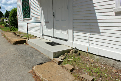 Photo 5. East wall with occasionally used doors: bad grade, sidewalk, step, and border, all to be improved.