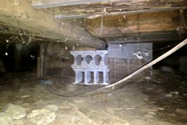 Photo 9. Ground-level floor frame: inadequate crawl space; concrete inappropriately poured around girt and floor joists for elevator support.