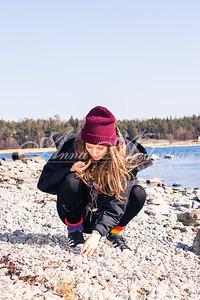 Plockar sten på stranden