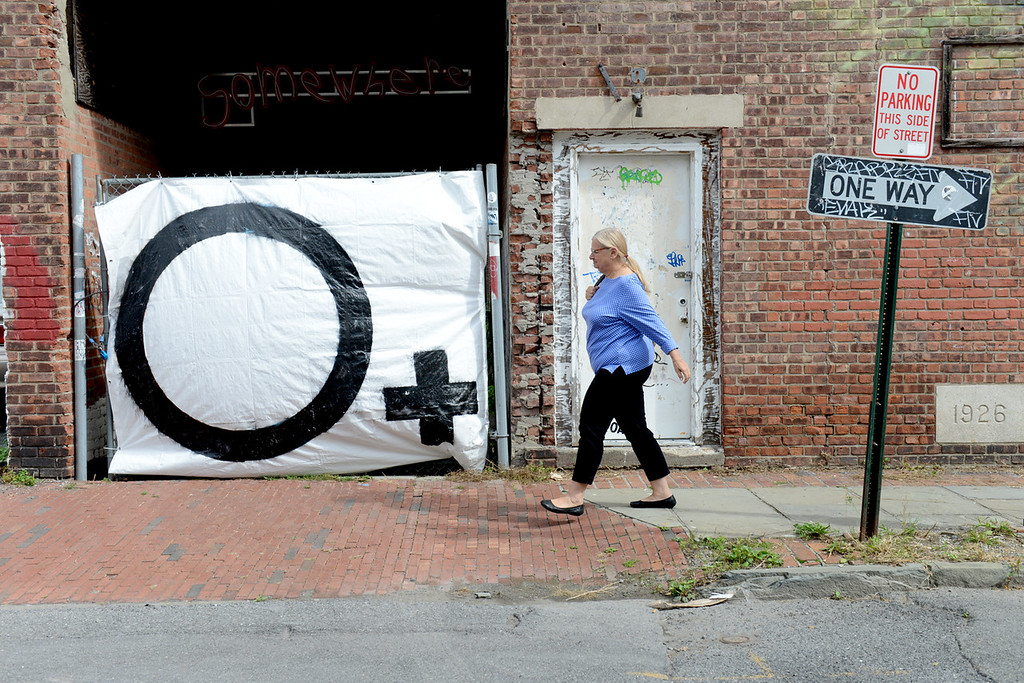 . Tania Barricklo-Daily Freeman Lorraine Keogh, who works in Uptown Kingston, walks past an O Positve banner on Crown St.
