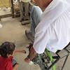Pablo Ruiz and his small helper, Malachai demonstrating the bicycle wheel driven machine that de-kernals corn cobs