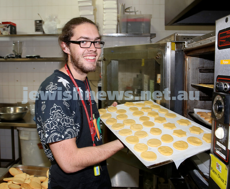 Volunteers at OBK make food packs for the French Embassy. Fletcher Deller places trays of biscuits in the oven.