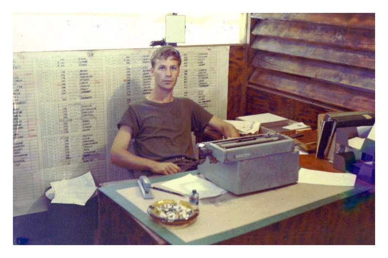 JRO-36: Roger O'Bryan, Company Clerk sitting behind his desk in Orderly Room at LZ Bayonet (July 1969) - Roger adds the following note: My old Royal typewriter used mostly for daily Morning Reports. I remember the x character wouldn't work which caused problems since the report had to be error free. Behind me was the Company roster which identifed individuals assigned to their respective platoons and squads. If I remember correctly, grease pencils were hard to come by.