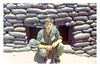 JRO-06: Joseph R. (Roger) O'Bryan (Louisville, KY) squatting in front of bunker.  Roger was the the unit clerk for most of 1969 and took great care of the Gunfighters in the field.