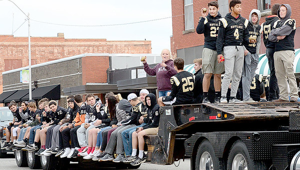Kevin Harvison | Staff photo<br /> Members of the 2017 McAlester Buffalo football team ride on the back of a flat bed semi-trailor down Choctaw Avenue Tuesday evening during the Home Coming Parade.