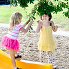 Kevin Harvison | Staff photo <br /> Washington Early Childhood Center students Abby Seamen, left and Kinzy Ania Lescher enjoy looking over some leaves during a Headstart recess.