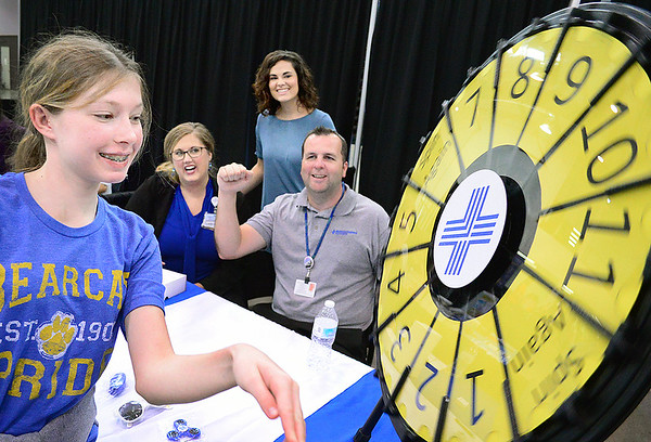 Kevin Harvison | Staff photo<br /> Pictured from left, Madison Sorrells, Antlers student, spins a prize wheel from the McAlester Regional Hospital booth, as MRHC employees Heather French, Ashley Kennon and Christopher Plunkett cheer her on during the Career Fair at the Southeast Expo Thursday.