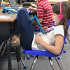 KEVIN HARVISON | Staff photo<br /> Emerson Elementary student Lillie McDowell, foreground, gets into a relaxed reading position while doing some classroom work.