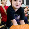 KEVIN HARVISON | Staff photo<br /> Emerson Elementary student Derick Williams reaches down deep into a pumpkin to feel the insides during a hands on lesson about pumpkins.