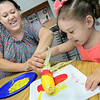 KEVIN HARVISON | Staff photo<br /> Shanna Twyman, left, helps Washington Early Childhood Center student Faneisha Redway with some corn art.