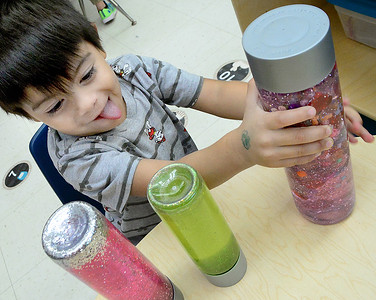 KEVIN HARVISON | Staff photo Washington Early Chidhood Center student Ezekiel Ponce thinks about which sensory bottle he likes the best.