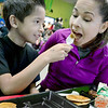 KEVIN HARVISON | Staff photo<br /> Emerson Elementary student Samuel Lopez, left, gives his mother Maricela Lopez a bite of his pancake during the Pancake for Parents event Wednesday morning at Emerson.