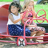 KEVIN HARVISON | Staff photo<br /> Pictured from left, Paisley Bark and Zoie Burse enjoy the weather while out for an imaginary drive at the Jefferson Early Childhood Center playground equipment.