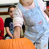 KEVIN HARVISON | Staff photo<br /> Gi'onah Lawrence reaches into a pumpkin to pull out the guts during a Emerson Elementary School pumpkin lesson.