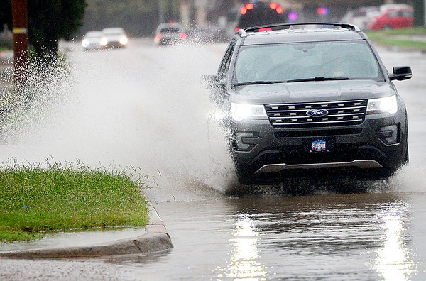 KEVIN HARVISON | Staff photo<br /> A vehicle makes its way down Wyndotte towards Sixth Street Tuesday morning after heavy rain hit the area.