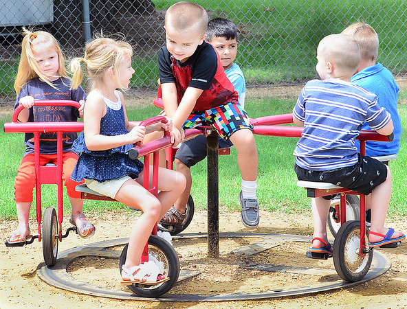 KEVIN HARVISON | Staff photo<br /> Daisi Hass, second from left, talks with Christopher Hughes, center, as he rides while the rest of the kids peddle the playground equipment.