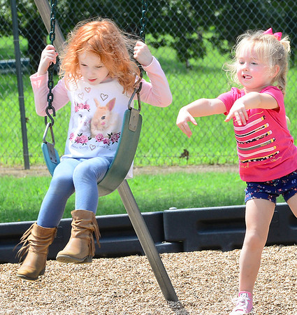 KEVIN HARVISON | Staff photo<br /> Mayce McCoy, left, gets a boost on the swing from Annabella Hackler.