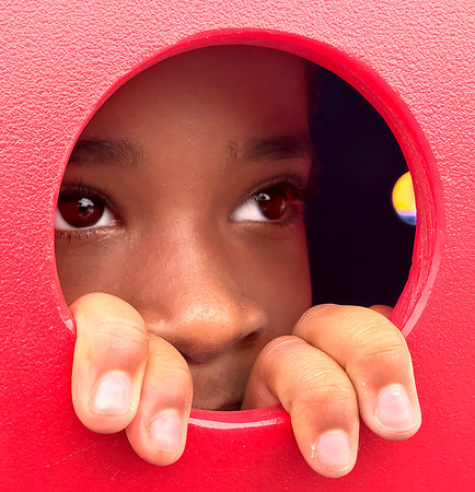 KEVIN HARVISON | Staff photo<br /> Gi'onah Lawrence looks through a vented area on a tunnel at Chadick Park.