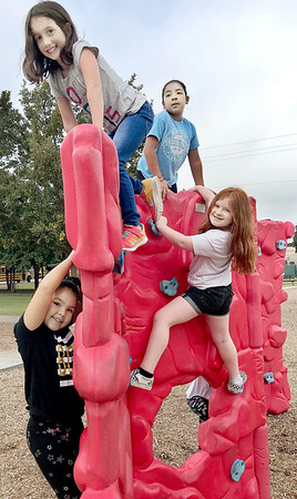KEVIN HARVISON | Staff photo<br /> Children take advantage of a recent visit to Chadick Park as the children climb on a piece of the playground equipment.