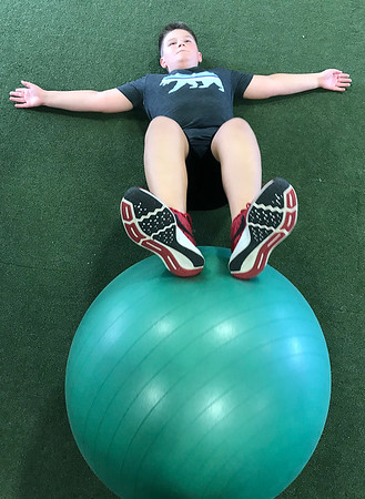 KEVIN HARVISON | Staff photo<br /> Cole Evans works his core during an after school program at Signature Fitness.