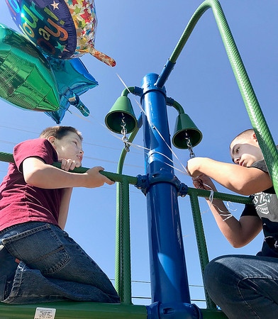 KEVIN HARVISON | Staff photo<br /> Pictured from left, Ian Northam and his brother Dalton Northam look over the balloons tied on the new playground equipment for the Parker students.