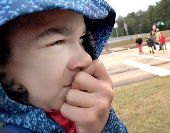 KEVIN HARVISON | Staff photo<br /> Aaron Hall shields himself from the cool breeze blowing on his way to school Tuesday morning.