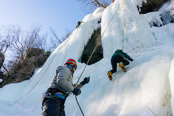 Start of an ice climb. Belayer in action pulling extra slack.