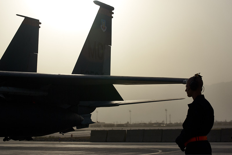An airman getting an F-15E ready before takeoff
