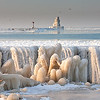 Ice on the break wall from the Coast Guard station.  Frozen lighthouse in the distance.