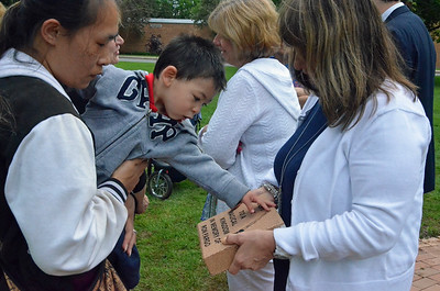 Leah McDonald - Oneida Daily Dispatch Camryn Smith, 22 months, examines a brick paver in honor of his grandfather Ron Fargo, while his mother Anna Smith holds him following a ceremony on Tuesday, May 30, 2017.