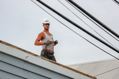 A worker for G&E Roofing pauses to watch the parade below on Main Street.
