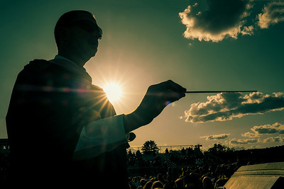 In Conrol: Kyle Jordan conducts the band at graduation in the setting sun.