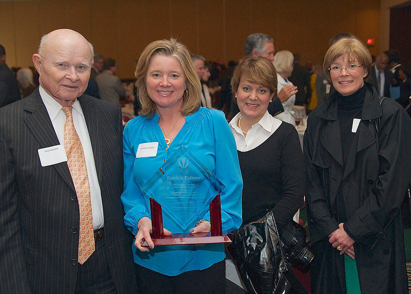 Surrounded by her family, Barbara Palmer (in blue) holds the award honoring her late husband Pat Palmer's contributions to soccer in Greensboro.