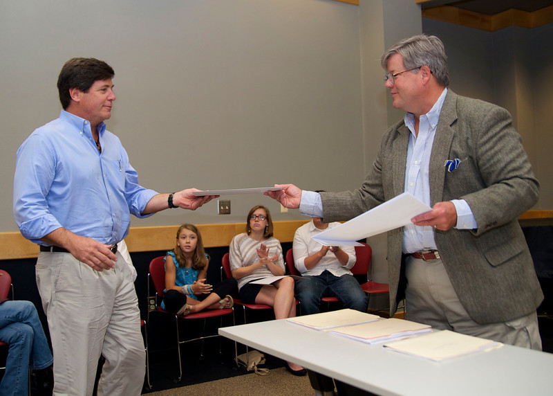 """O. Henry Magazine Editor Jim Dodson hands General Non-Student Category 3rd Place winner Chip Bristol his award for his story """"The Cabin""""."""