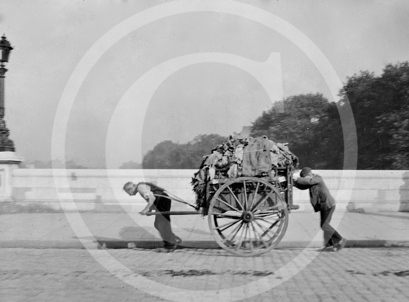 An elderly man pulling & a young man pushing a large 2 wheel cart loaded with rags on a cobblestone street in Paris 1920.